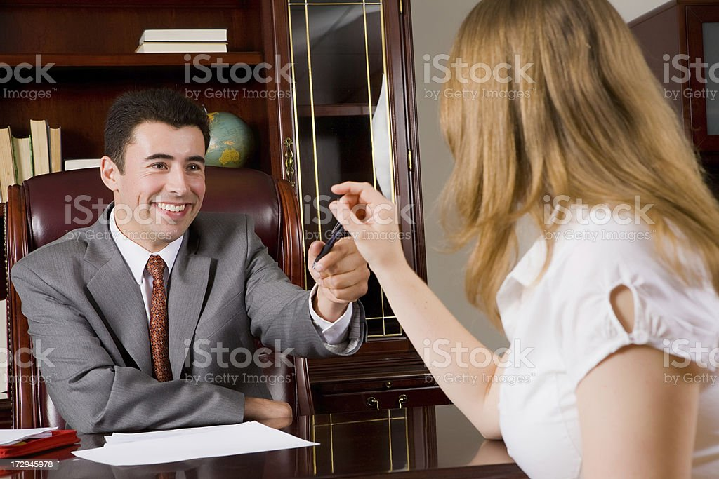 Business man handing a pen to his client royalty-free stock photo
