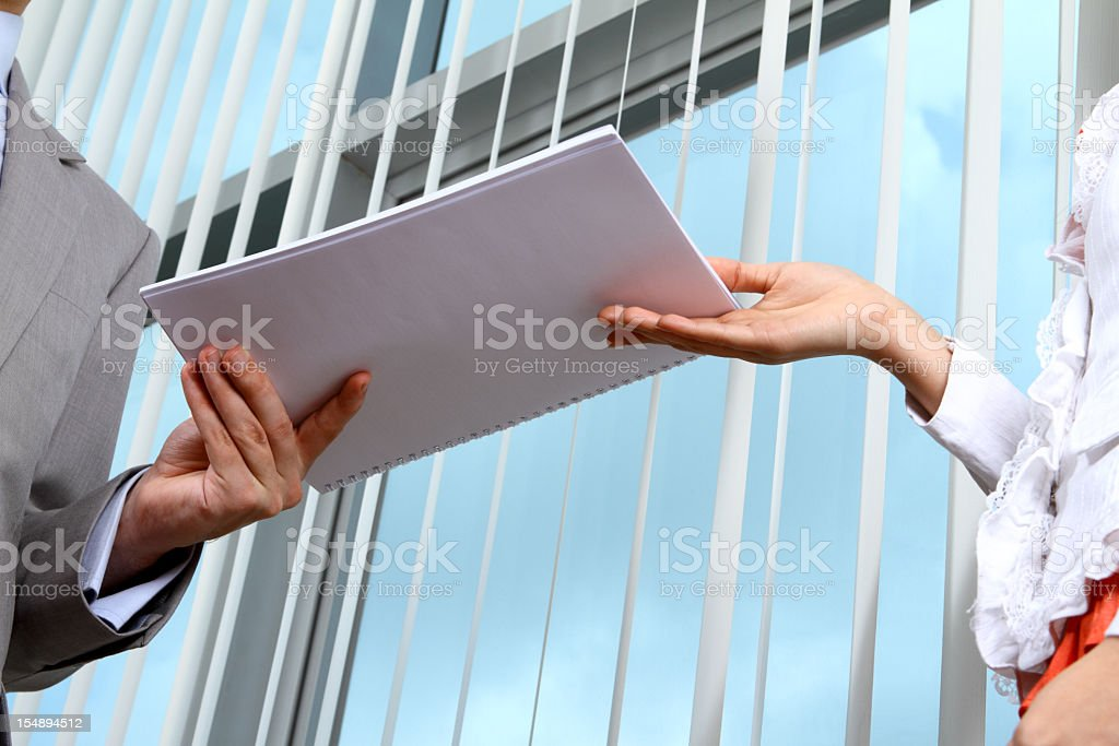 Business man handing documents over to his secretary stock photo
