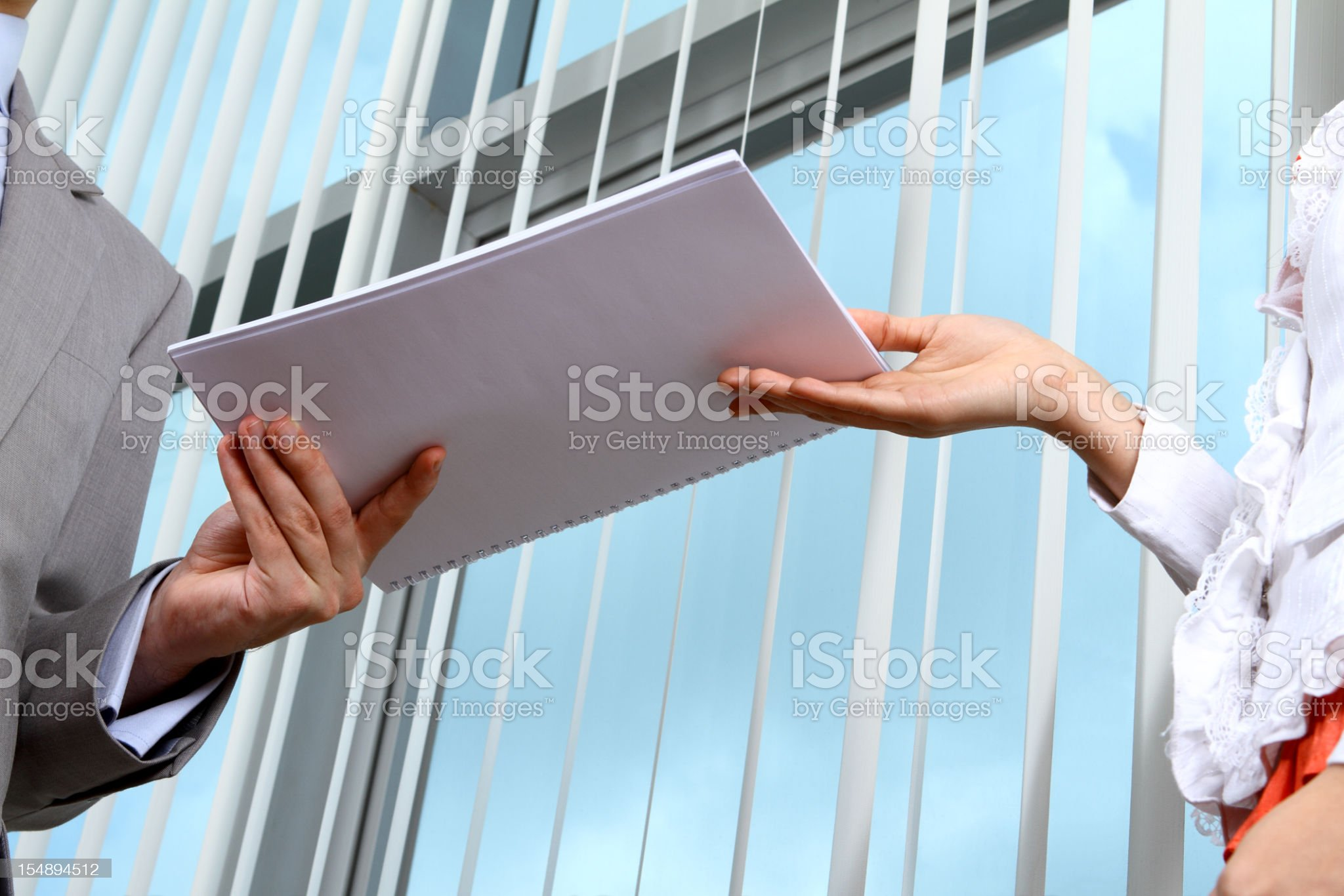 Business man handing documents over to his secretary royalty-free stock photo