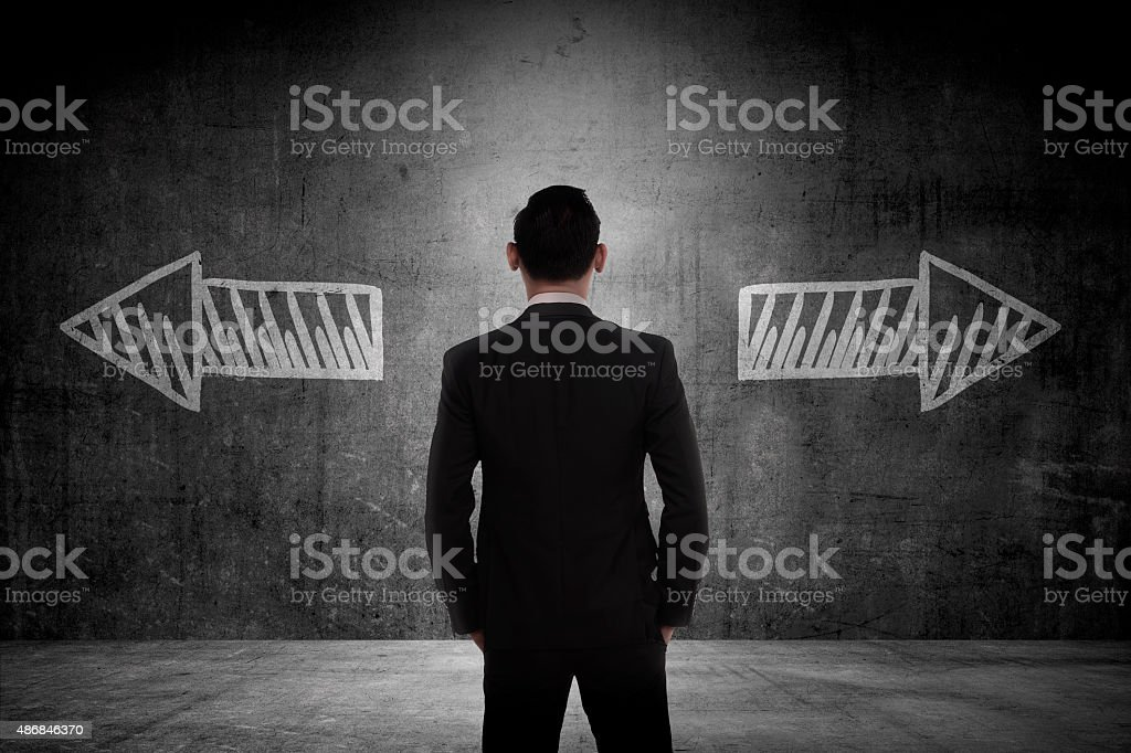 Business man has to choose between two way stock photo