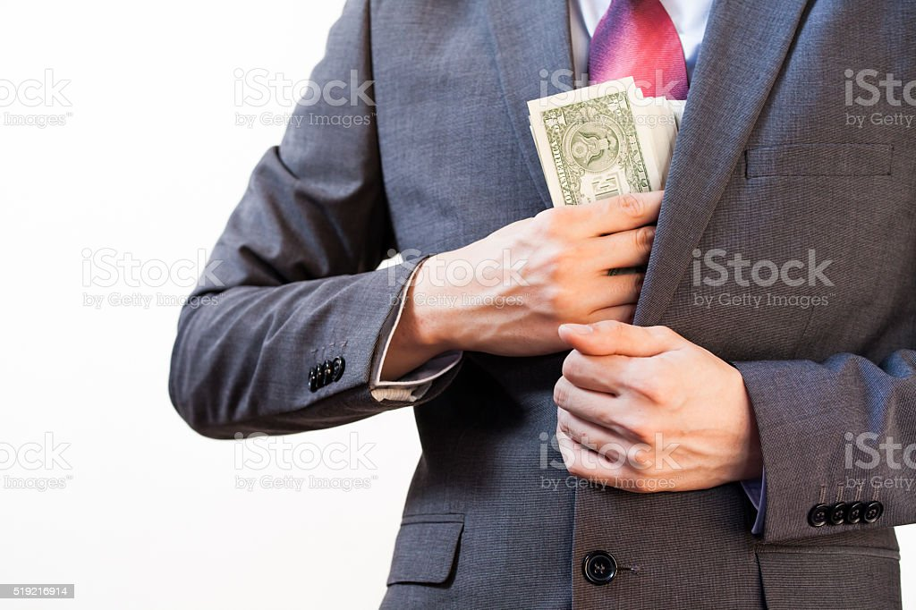 Business man hiding money in jacket pocket stock photo