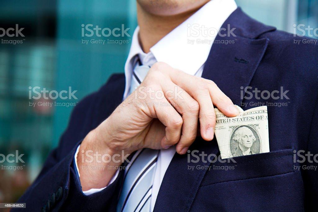 Business man hiding money in pocket stock photo