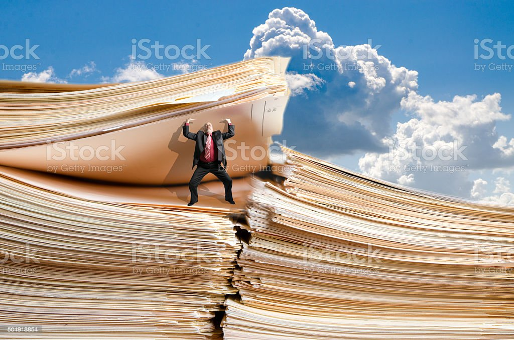 Business man holding a giant pile of files stock photo