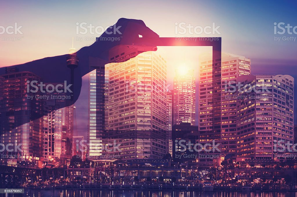 Business man holding a picture frame over city. stock photo