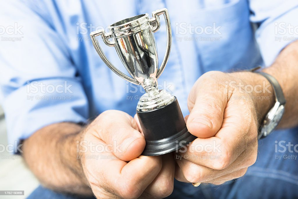 Business man holding a silver Trophy stock photo