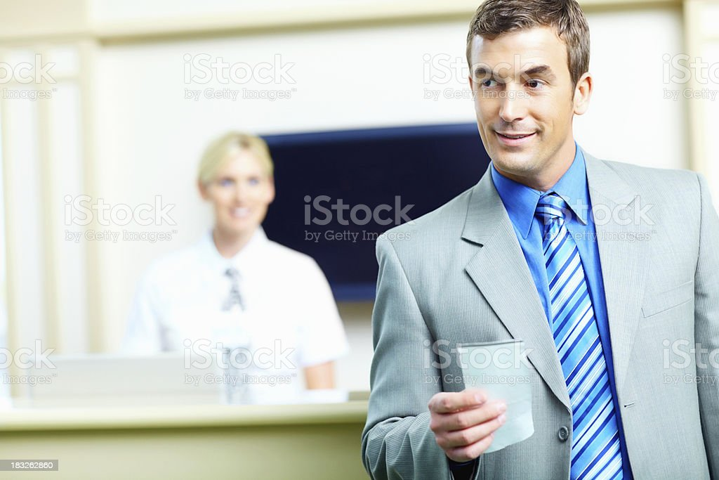 Business man holding a ticket with receptionist in background stock photo