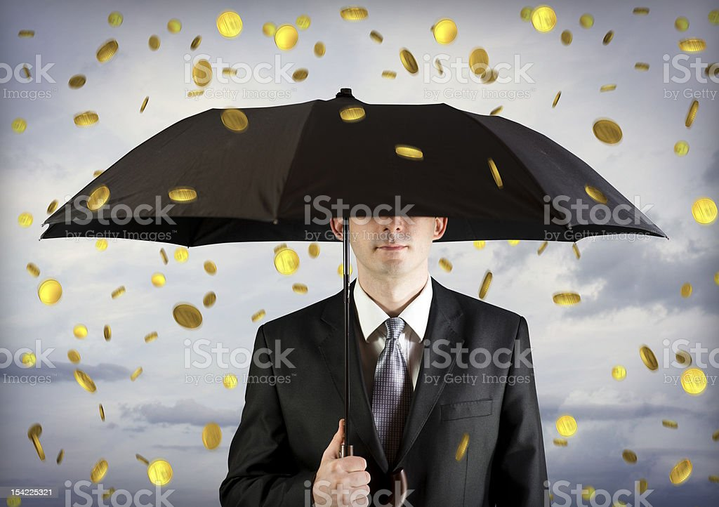 Business man holding an umbrella, money falling from the sky stock photo