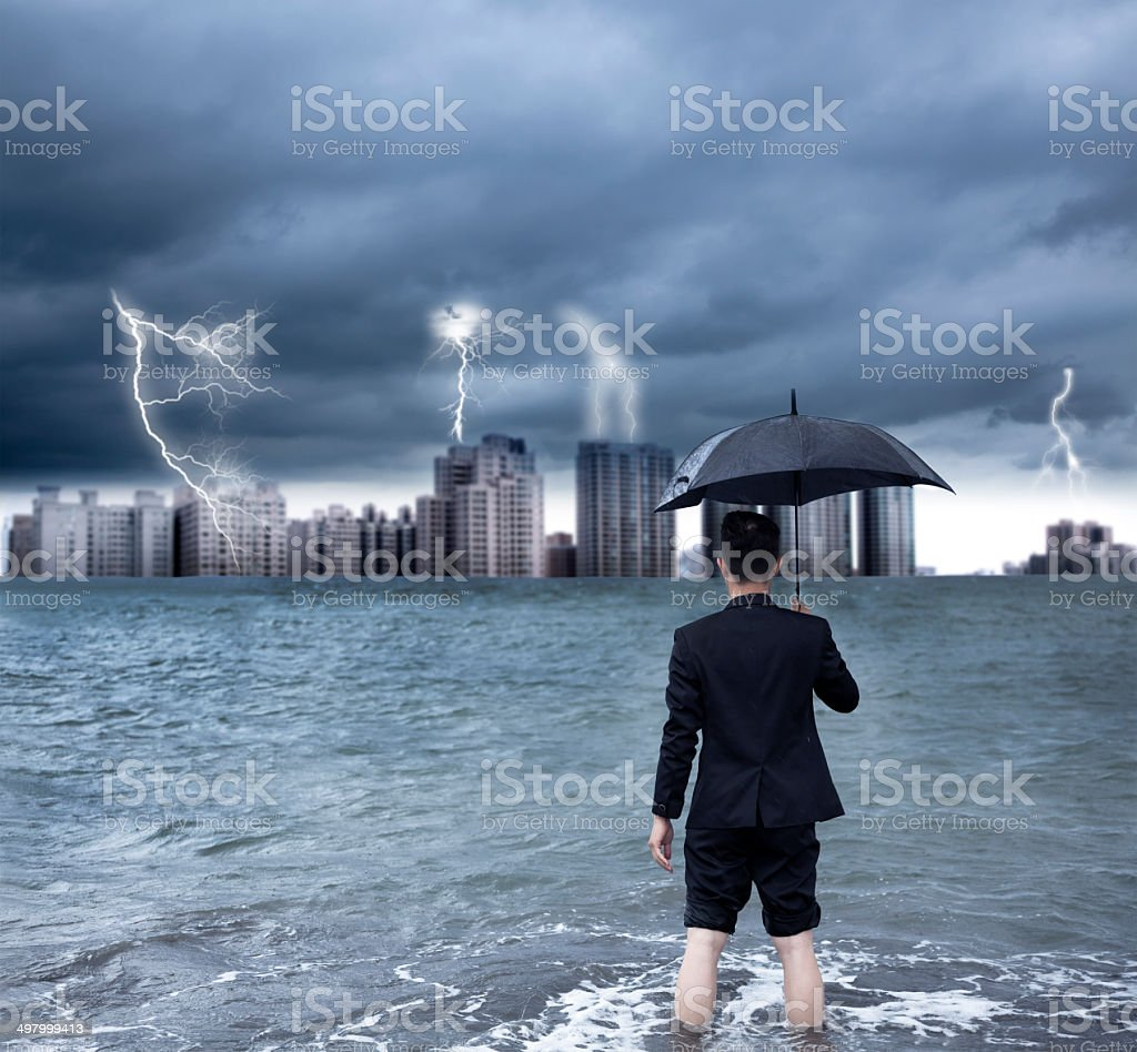 business man holding an umbrella with thundershower background stock photo