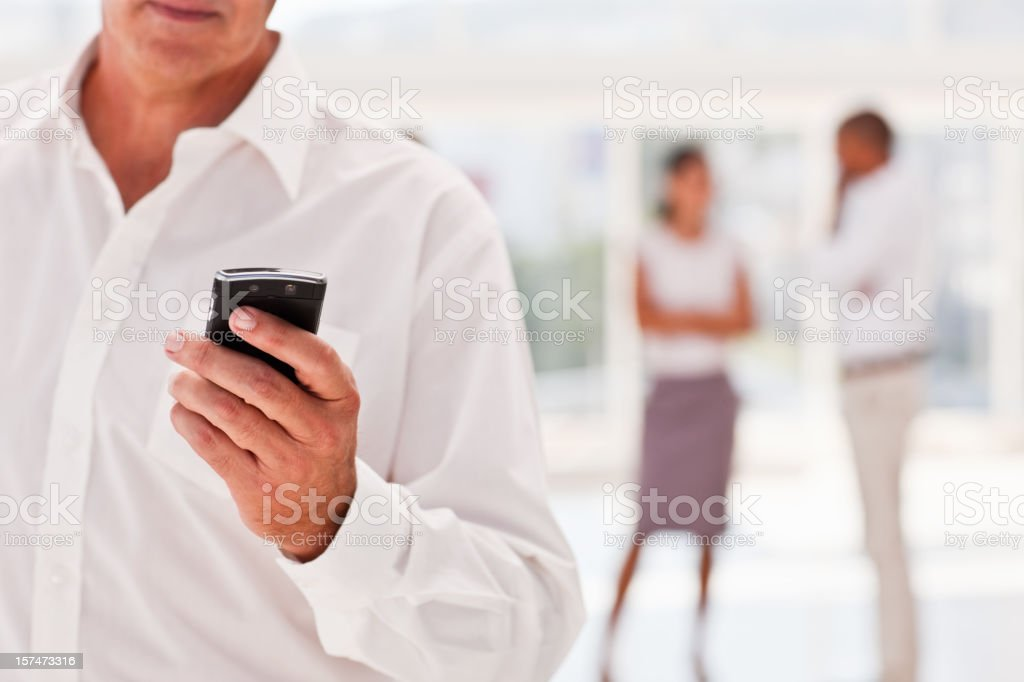 Business man holding cellphone with partners at the back royalty-free stock photo