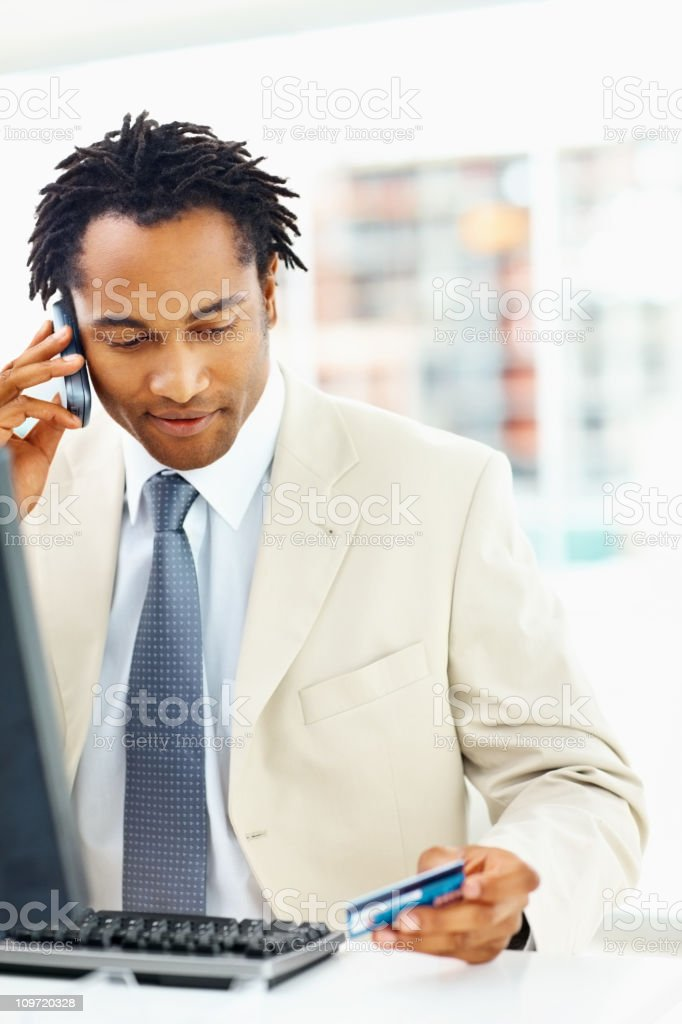Business man holding credit card while talking on the phone royalty-free stock photo