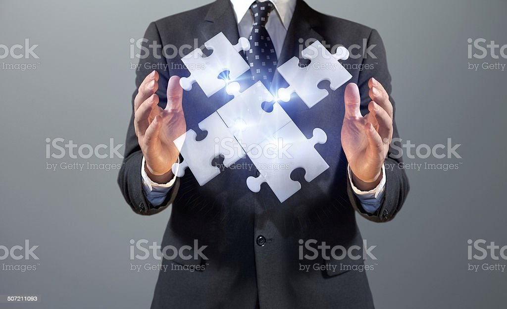 Business man holding floating jigsaw puzzle with connecting pieces stock photo