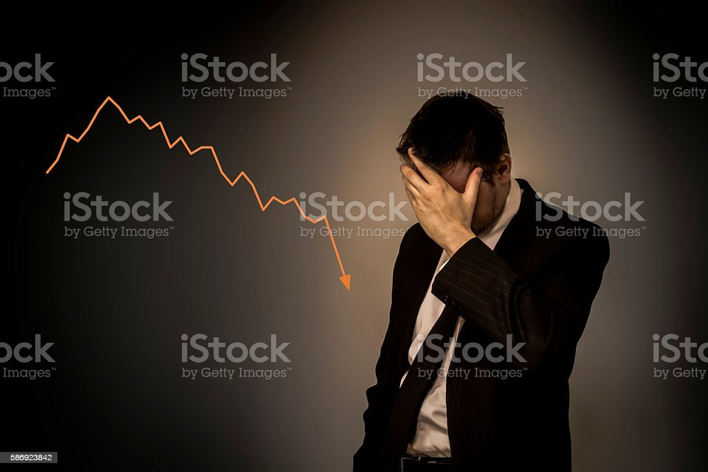 Business man holding hand on his face with falling graph stock photo