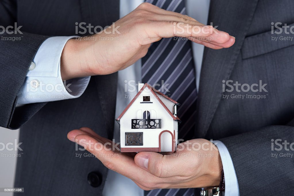 Business man holding house model stock photo