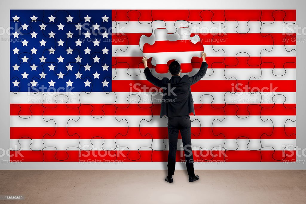 Business man holding piece of puzzle, making USA flag stock photo