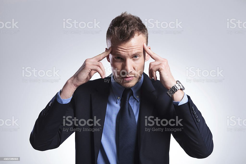 business man holds fingers at temples stock photo