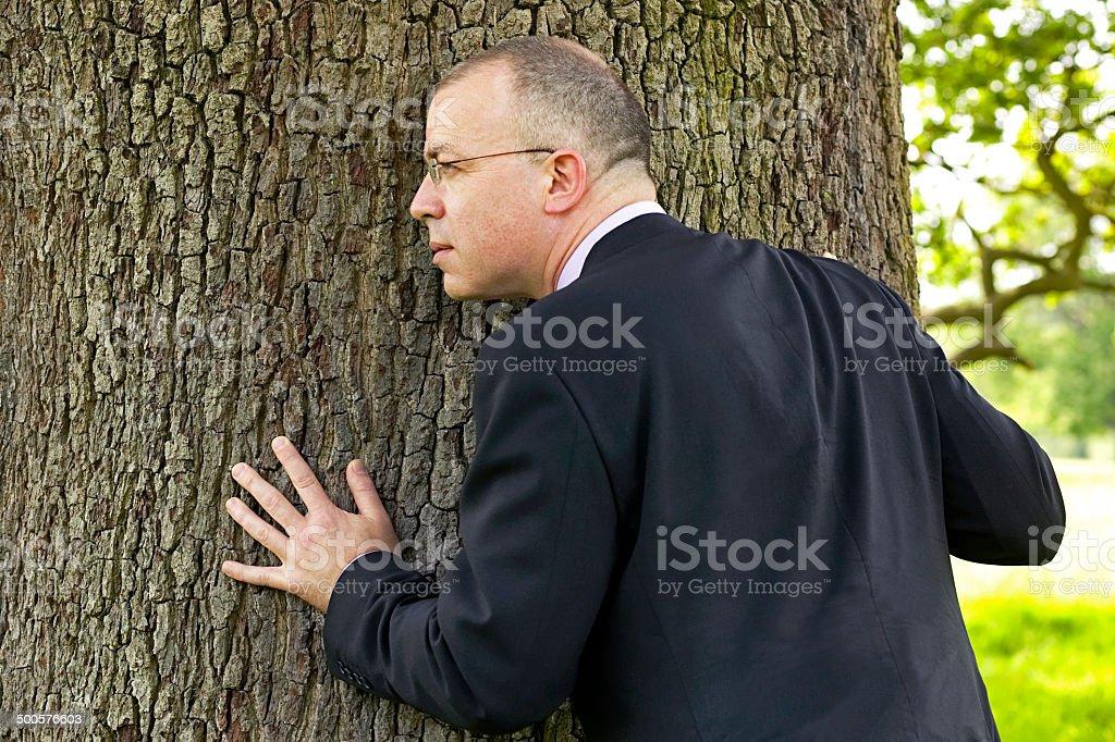 Homme d'affaires se tenant un arbre et écoute photo libre de droits