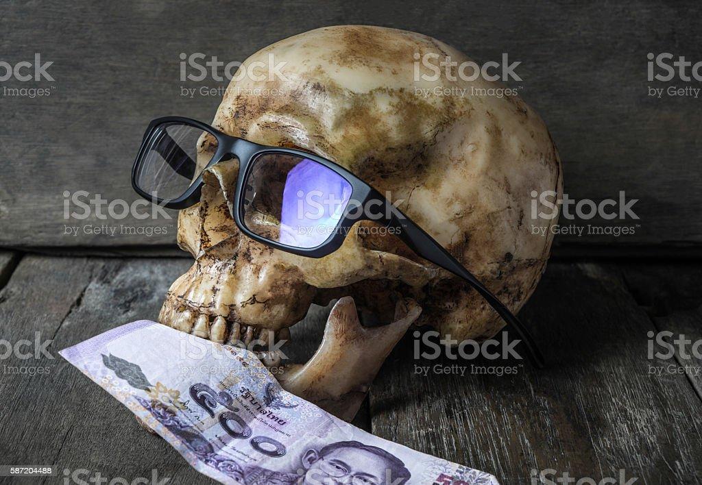 Business man Human Skull eating Money stock photo