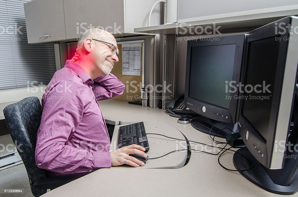 Business man in front of computer screens with neck ache stock photo