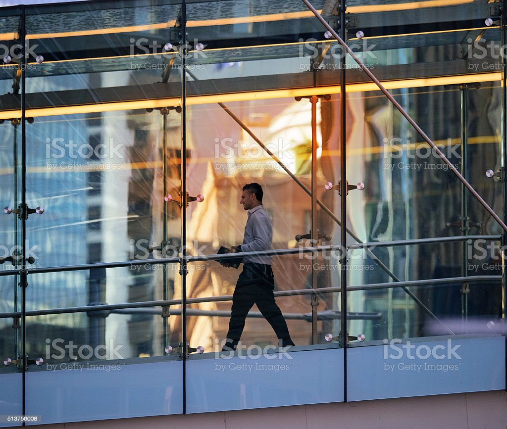 Business man in glass walkpath between office buildings stock photo