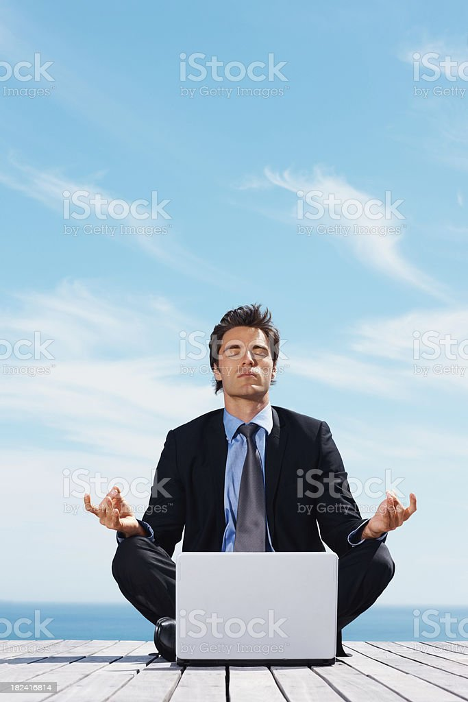 Business man in lotus position with laptop outside royalty-free stock photo