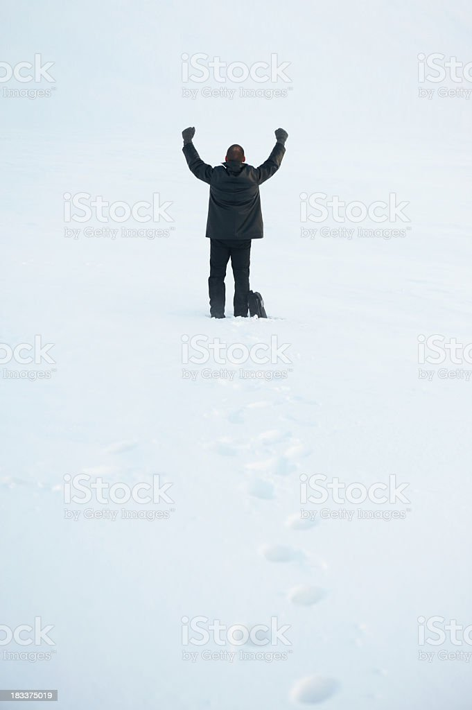 Business man in snow storm cheering or welcoming challenges royalty-free stock photo