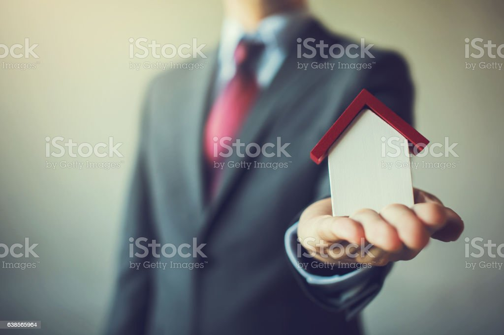 Business man in suit having miniature house on palm hand stock photo