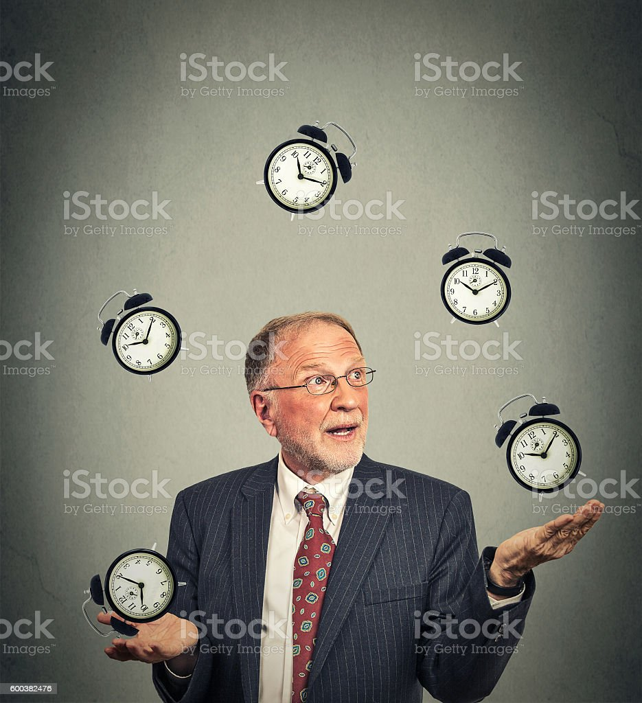 business man in suit juggling multiple alarm clocks stock photo