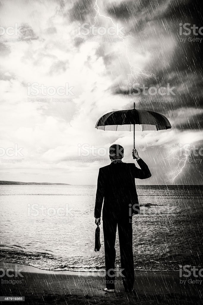 business man in the storm with umbrella stock photo