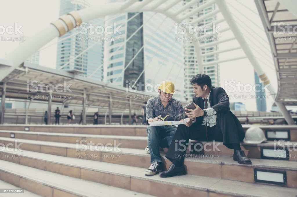 Business man is intend working with engineer stock photo