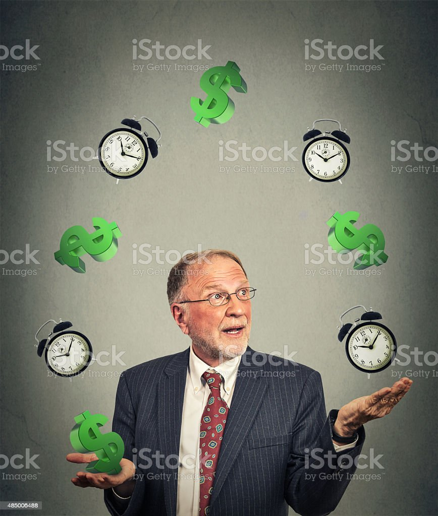 business man juggling multiple alarm clocks and dollar sings stock photo