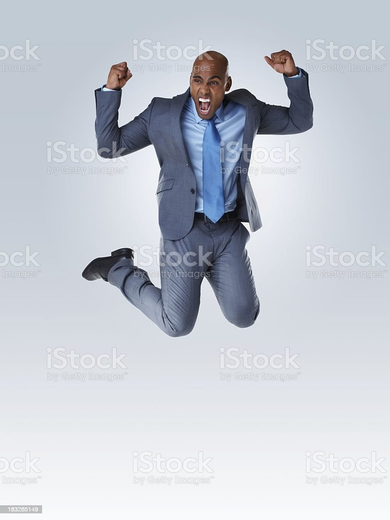 Business man jumping against colored background - copyspace royalty-free stock photo