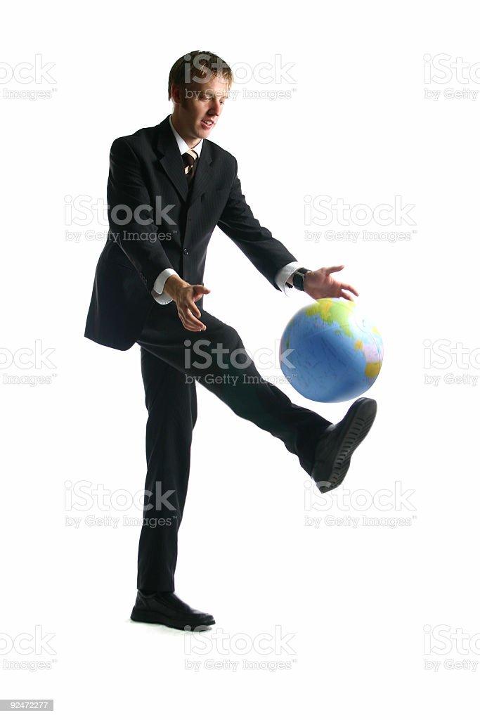 Business man kicking the globe stock photo
