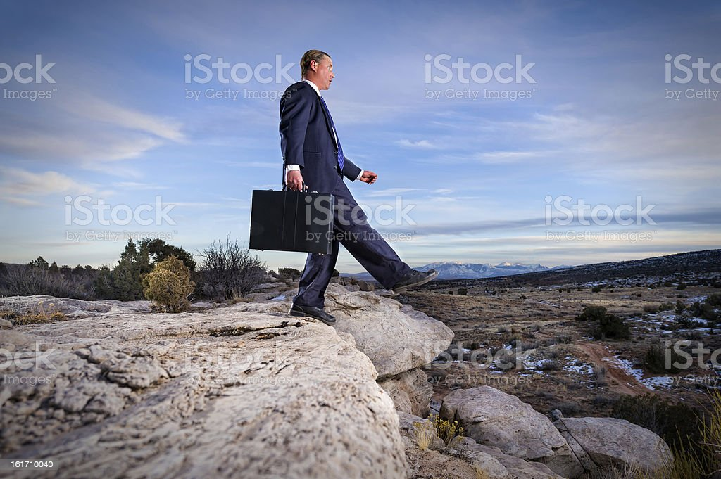 Business Man Leaping Off Fiscal Cliff stock photo