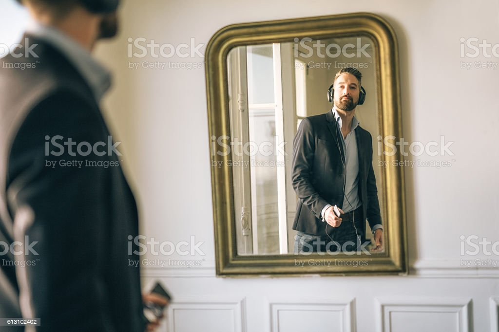 Business man listening music in front of mirror stock photo