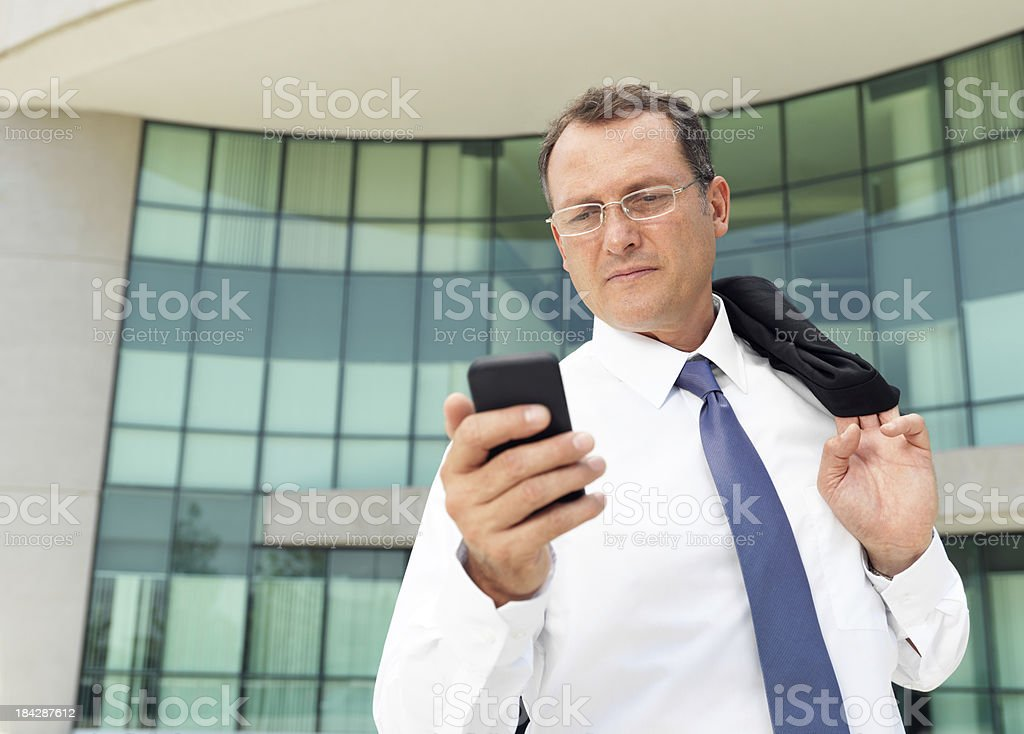Business man looking at his cellphone royalty-free stock photo