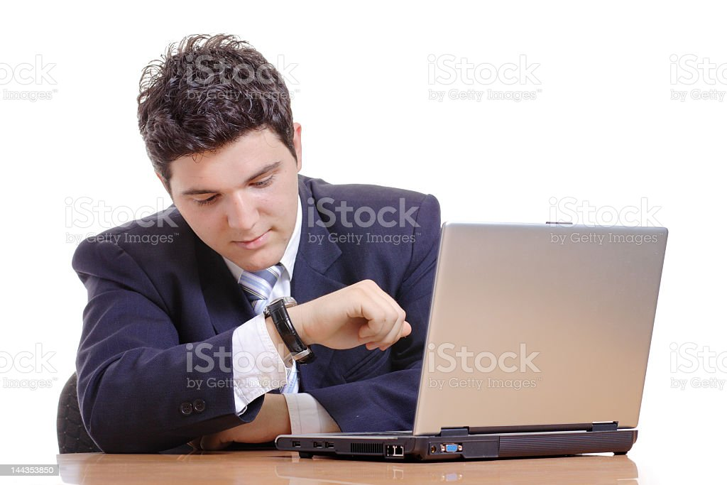 Business man looking at watch with laptop in front of him stock photo