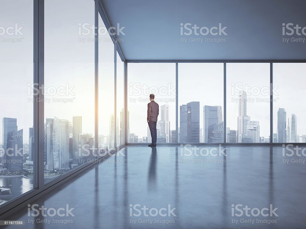 Business man looking megalopolis through window stock photo