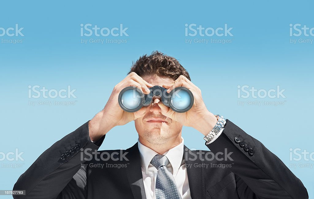 Business man looking through a pair of binoculars royalty-free stock photo