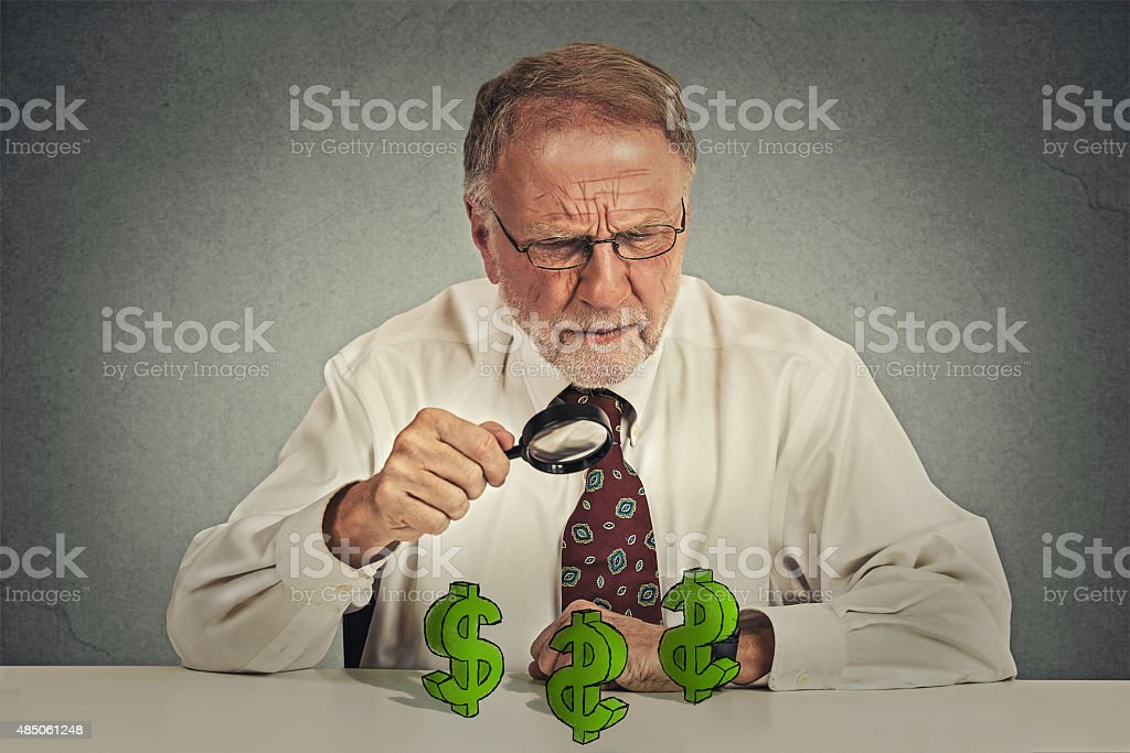 business man looking through magnifying glass at dollar signs stock photo