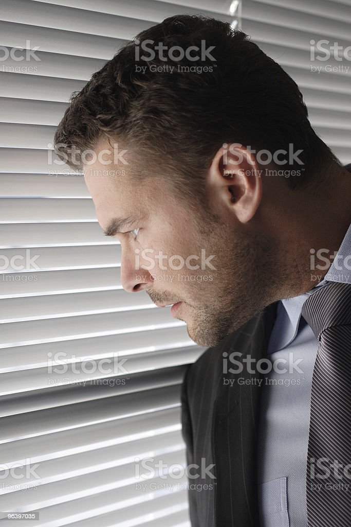 business man looking through window blinds royalty-free stock photo