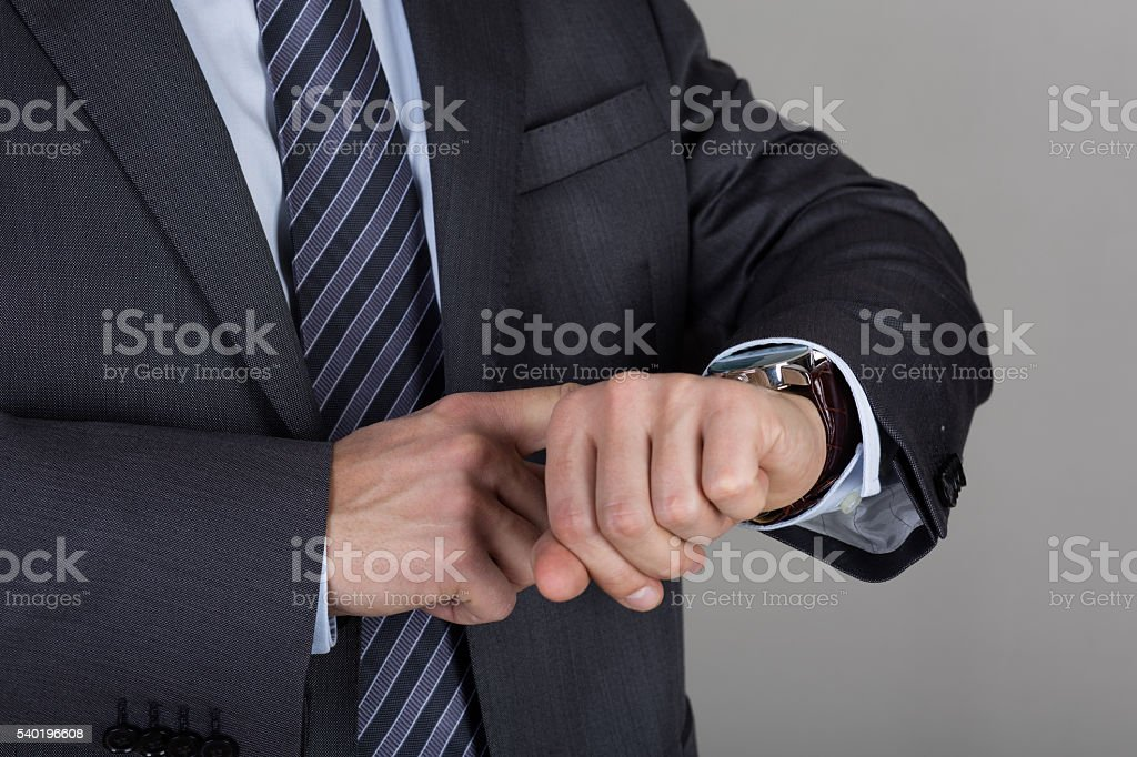 Business man looks at his wrist watch checking the time stock photo