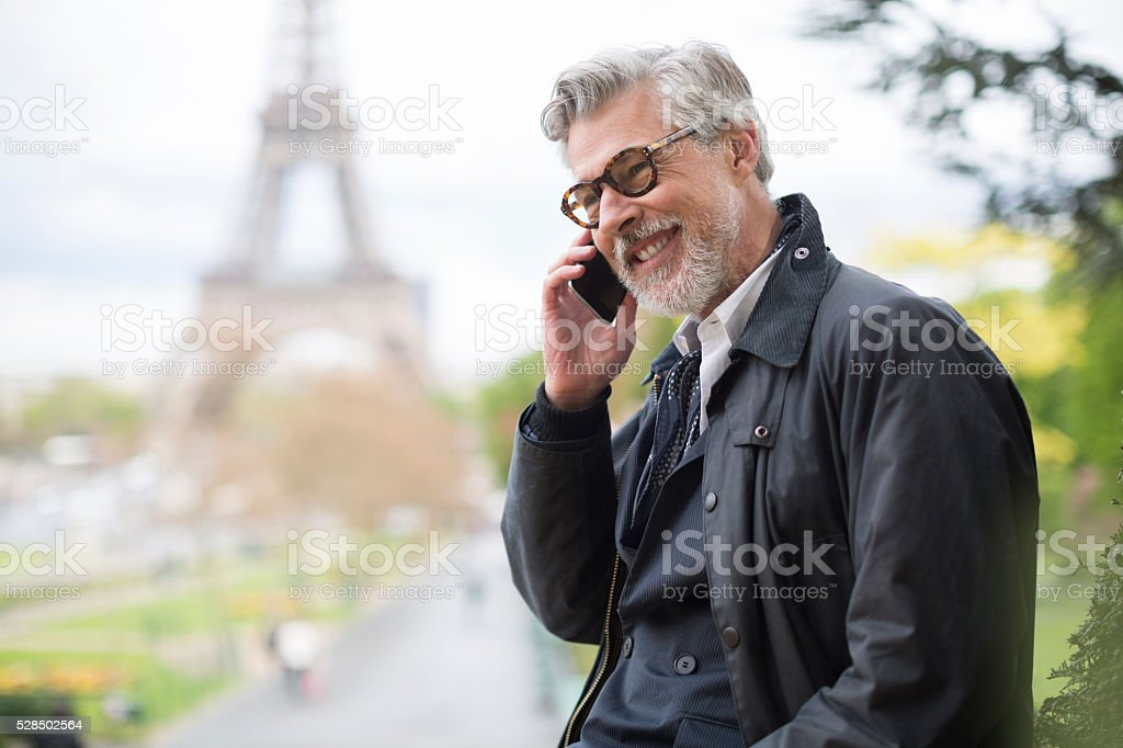Business man making a phone call near the Eiffel Tower. stock photo