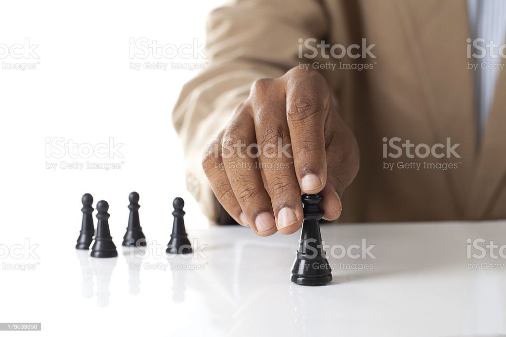 Business man moving chess figure with team behind stock photo