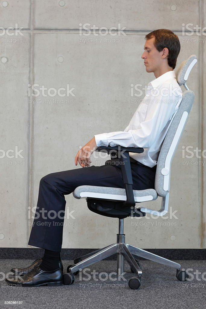 business man on chair in correct sitting position - resting stock photo