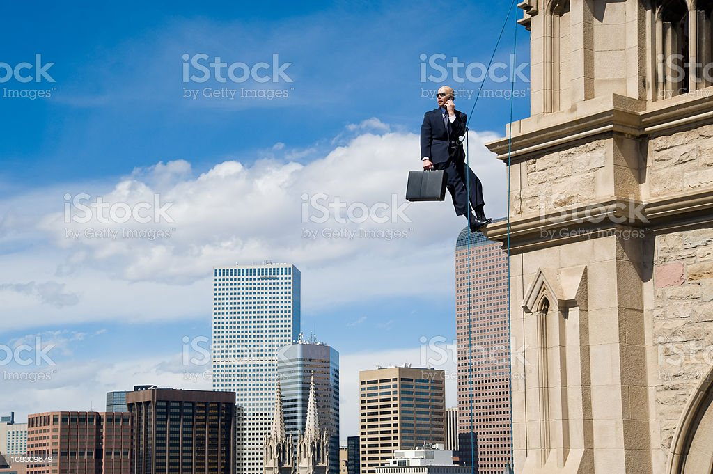 Business Man on Rope in Suit Hanging Off Building stock photo