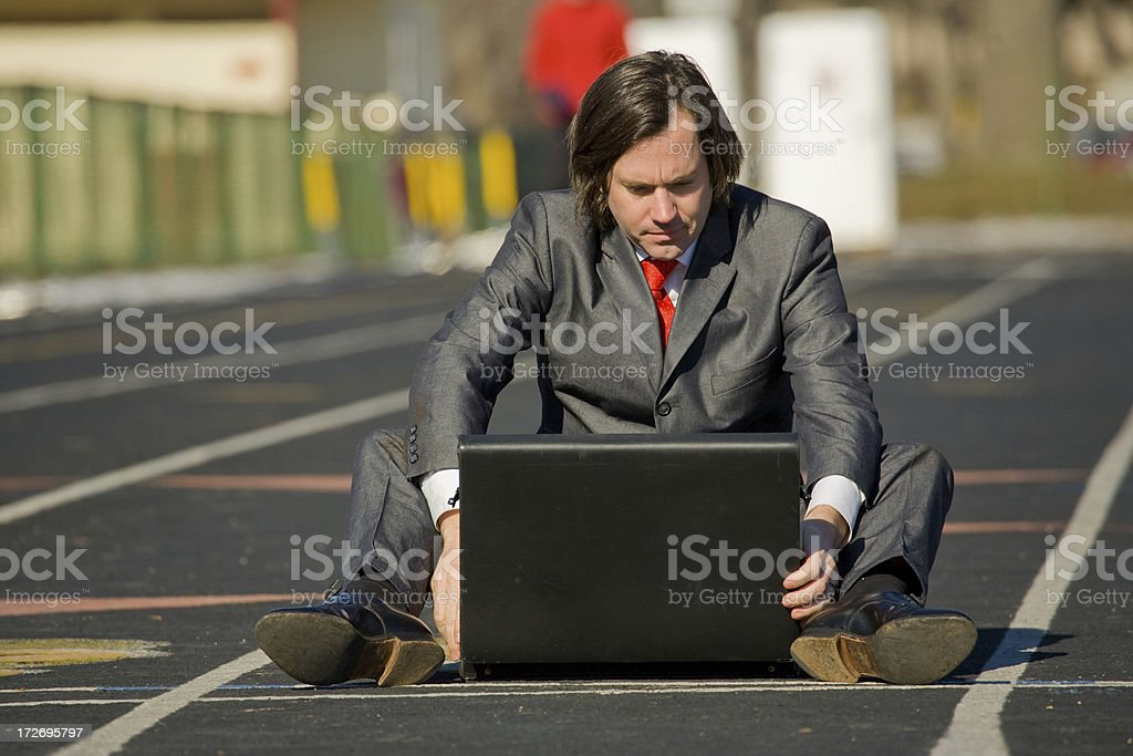 Business man on running track looks into briefcase royalty-free stock photo