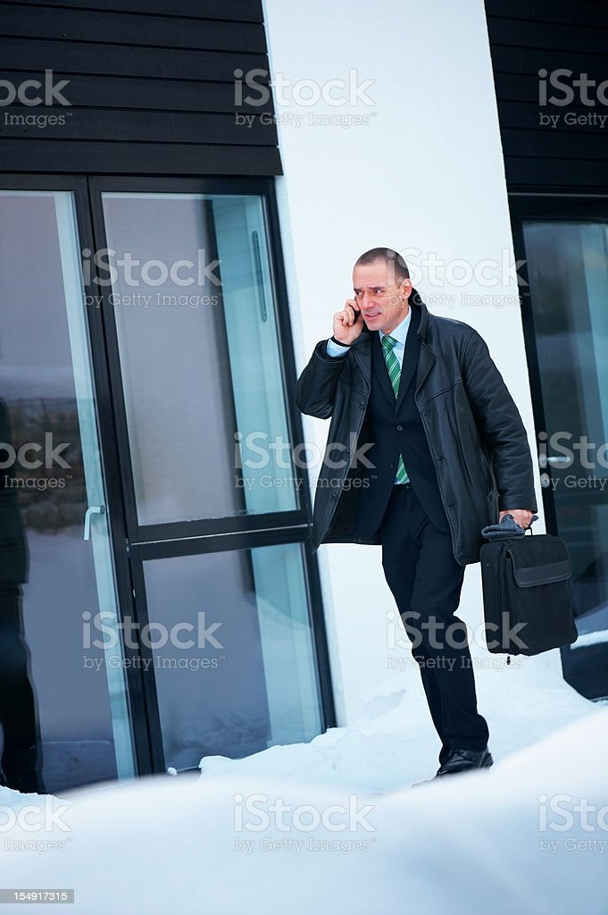 Business man outside stylish home in snow on the phone stock photo