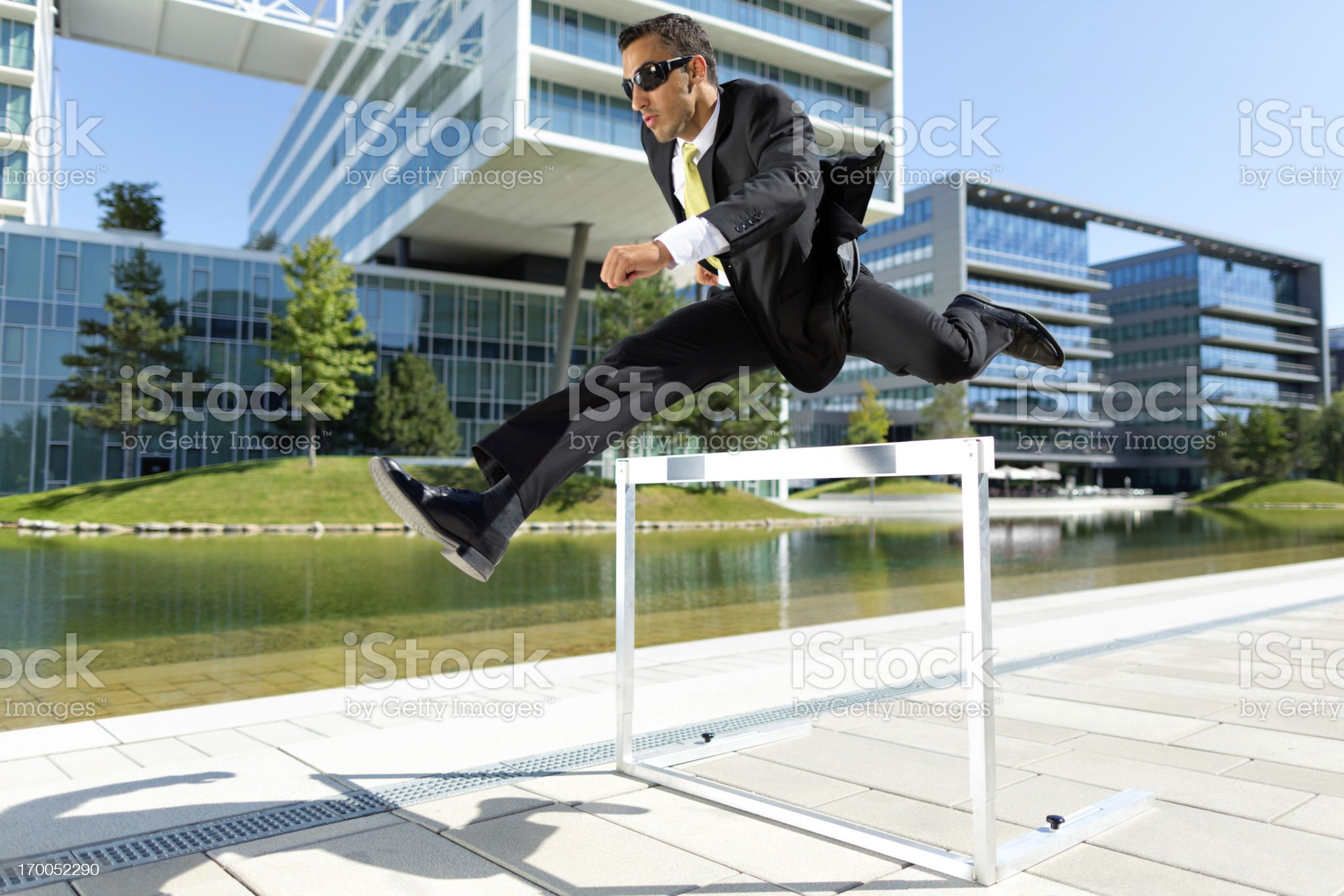 business man over hurdle near offices royalty-free stock photo
