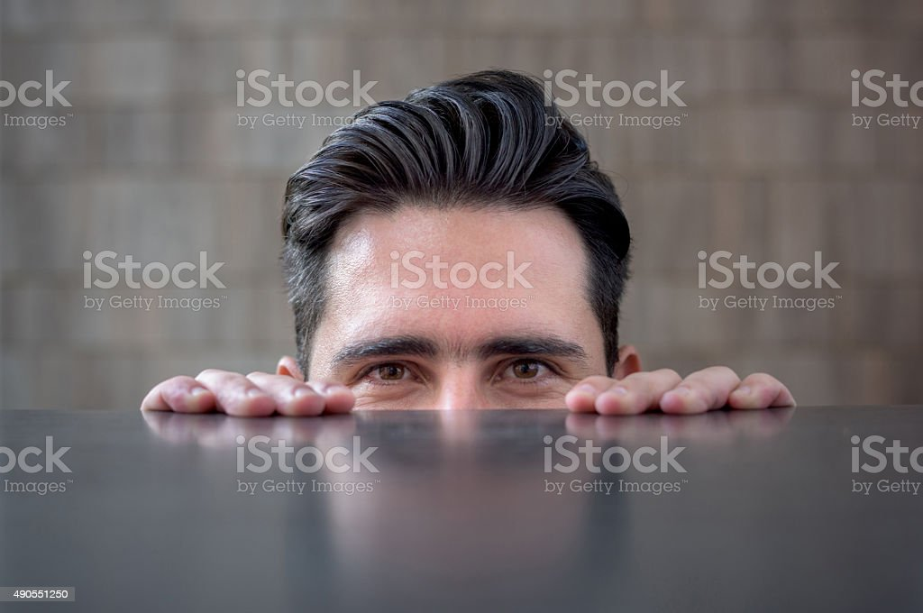 Business man peeking over a table stock photo