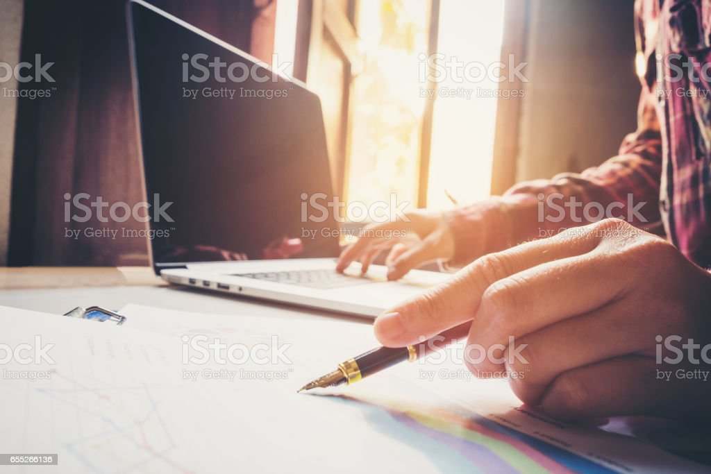 business man pointing his ideas Data and writing business plan at workplace,man holding pens and making notes in documents, on the table stock photo